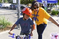A parent assists a student riding a bicycle at a bicycle safety rally